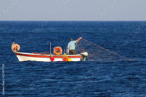 Greek fishermen using fishing nets on the boat