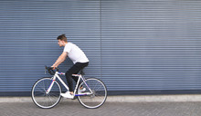 Young Man In A White T-shirt Rides On A White Highway On The Background Of The Wall. Portrait Of A Student Riding A Bicycle On The Background Of The Wall. Copyspace