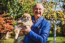 Senior Man With His Pet Little Red Pekingese Dog At Home Yard. American Mature Man With A Dog. Concept Of Life Animals And Human