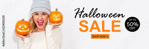 Fotografie, Tablou  Halloween sale with young woman holding pumpkins