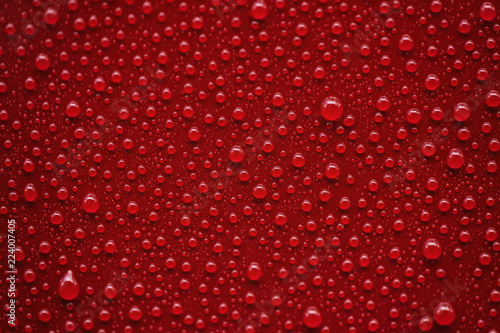 Closeup rain drops on red car with hydrophobic coating