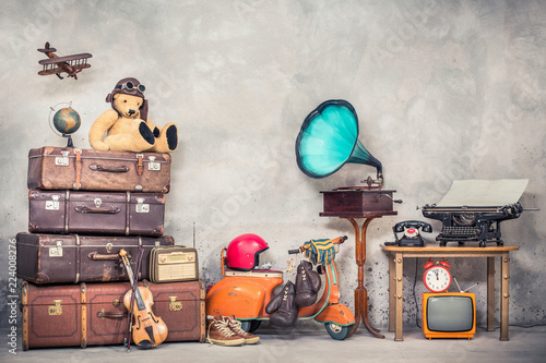 Scooter Retro Teddy Bear toy in aviator's hat, wooden plane, aged classic travel valises, globe, children pedal scooter, phonograph, typewriter, clock, TV, radio, old telephone. Vintage style filtered photo