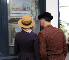 A Couple Of Romantic Lovers Look At The Windows In Montmartre In Paris