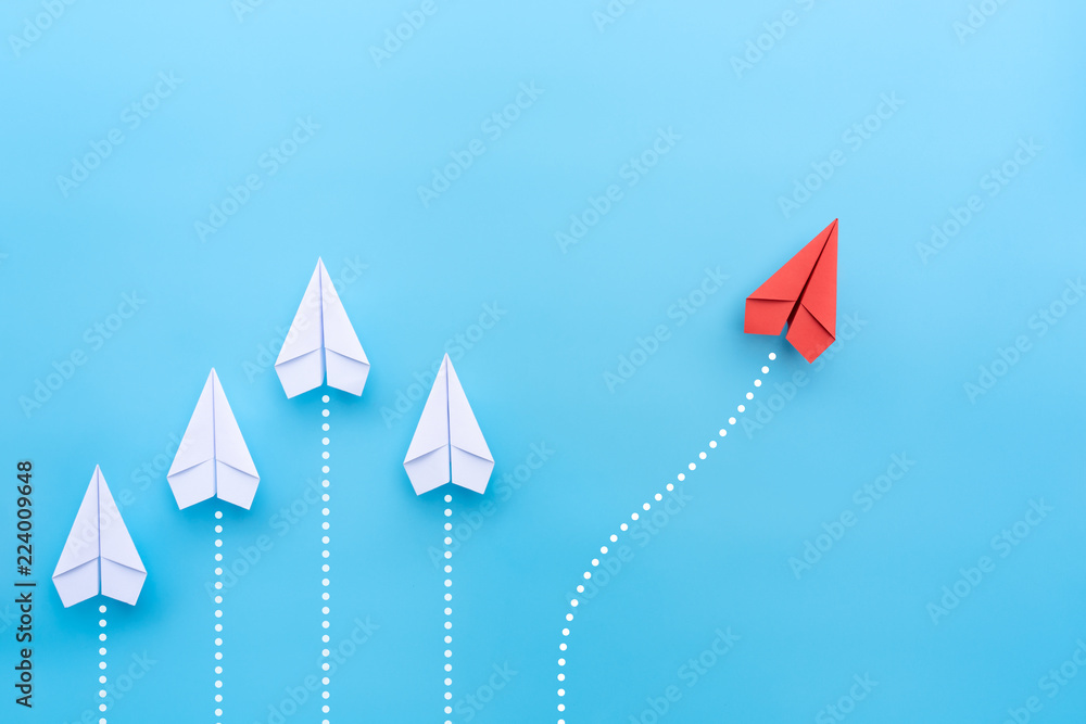 Fototapeta Group of white paper planes in one direction and one red paper plane pointing in different way on blue background. Business for new ideas creativity and innovative solution concepts.