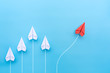 Leinwanddruck Bild - Group of white paper planes in one direction and one red paper plane pointing in different way on blue background. Business for new ideas creativity and innovative solution concepts.