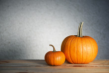 Two Pumpkins On Wooden Table. ...