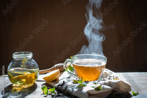 Garden Poster Tea Hot tea in glass teapot and cup with steam on wood background