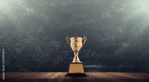 Fényképezés champion golden trophy placed on wooden table with blackboard background copy space ready for your design win concept