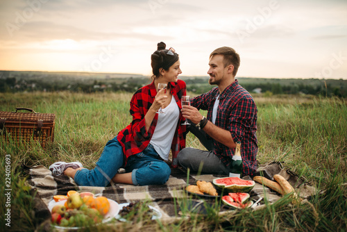 Love couple drinks wine, picnic in summer field