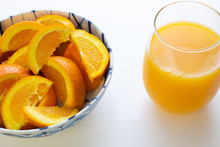 Freshly Squeezed Orange Juice In A Glass Next To A Bowl Of Orange Slices And Two Oranges Just Picked Off The Tree On A White Table For Breakfast.