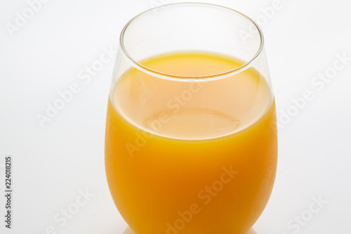 Fresh squeezed orange juice right off a tree into the glass on white kitchen tab Canvas Print