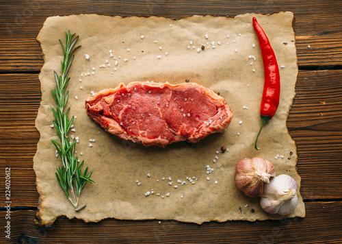 Staande foto Vlees Uncooked piece of meat on wooden table, top view