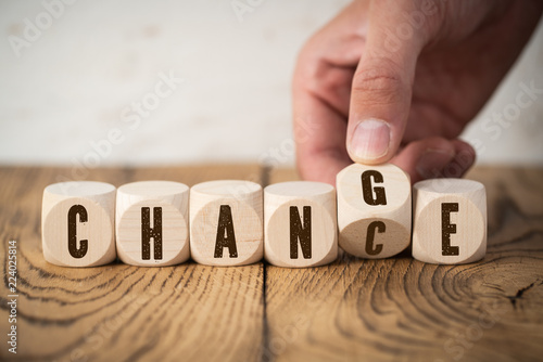 "Fotografía  Hand flips one of six cubes with letters, turning the word ""change"" to ""chance"""