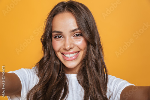 Photo Portrait of happy woman 20s with long hair laughing while taking selfie photo, i