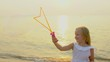 Happy cute Little Girl Playing wit Soap Bubbles outdoor on the beach during beautiful sunset happy vacation time in slow motion. Kid having fun in beach outdoors. Concept of travel, happy family, sea