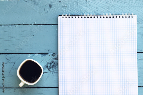 Fotografie, Obraz  coffe cup and notebook in blue table