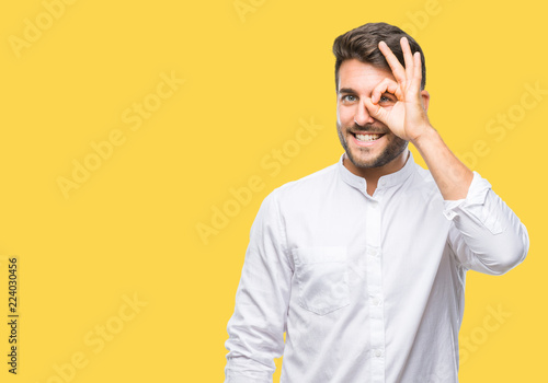 Fotografia  Young handsome man over isolated background doing ok gesture with hand smiling, eye looking through fingers with happy face