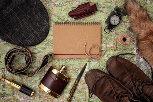 Flat lay with hunting ammunition over the map as background: old boots, hat, knife, rope, belt, fox tail.