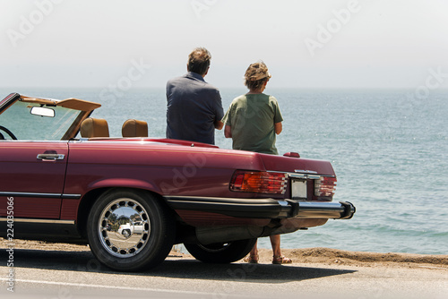 Photo  A middle aged couple with parked convertible car, looking at Pacific ocean near
