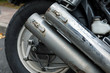 Close-up of motorcycle wheel and double exhaust pipe