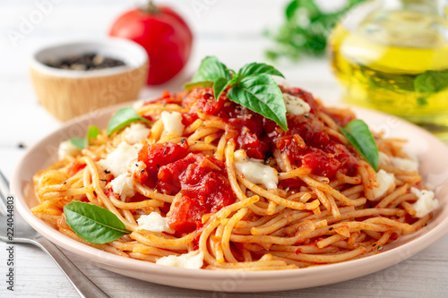 Spaghetti pasta with tomato sauce, mozzarella cheese and fresh basil in plate on white wooden background Billede på lærred