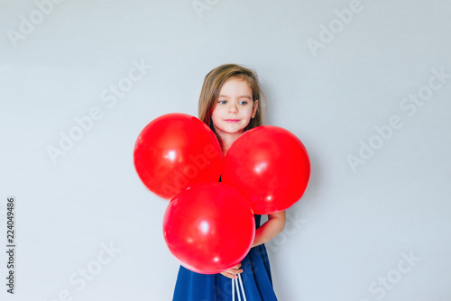 Photo  Happy funny girl with red balloon near empty grey concrete walls