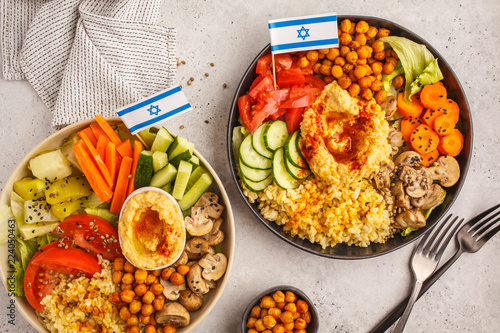 Buddha bowls with vegetables, mushrooms, bulgur, hummus and baked chickpeas. White background, top view. Israeli food concept.