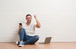 Young caucasian man sitting over white brick wall using computer laptop and smartphone annoyed and frustrated shouting with anger, crazy and yelling with raised hand, anger concept