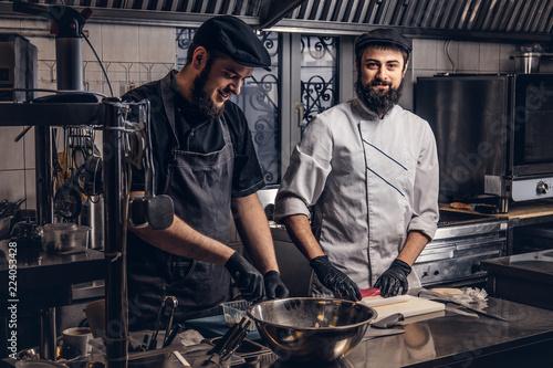 Obraz na płótnie Two smiling bearded cooks dressed in uniforms preparing sushi in the kitchen