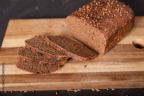 Fotografie, Obraz  A sliced brown loaf of bread on a chopping board.