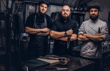 Team Of Professional Bearded Cooks Dressed In Uniforms Posing With Knives In Kitchen.