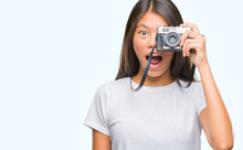 Young Asian Woman Holding Vintagera Photo Camera Over Isolated Background Scared In Shock With A Surprise Face, Afraid And Excited With Fear Expression