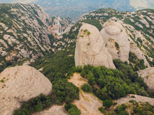 Montserrat, Catalonia, Spain. Top View Of Hillside Cave Santa Cova De Montserrat Or Holy Cave Of Montserrat In Summer Day.
