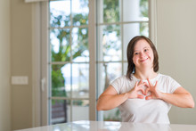 Down Syndrome Woman At Home Smiling In Love Showing Heart Symbol And Shape With Hands. Romantic Concept.