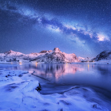 Milky Way Above Frozen Sea Coast And Snow Covered Mountains In Winter At Night In Lofoten Islands, Norway. Arctic Landscape With Blue Starry Sky,  Water, Ice, Snowy Rocks, Milky Way. Beautiful Space