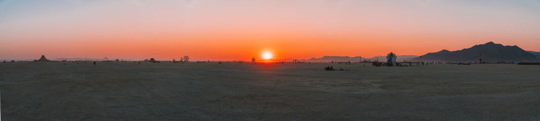 Amazing sunrise view over the desert with people walking on the horizon