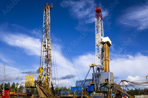 Fotografia  Oil and Gas Drilling Rig onshore dessert with dramatic cloudscape