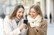 canvas print picture - Excited friends reading phone content in winter