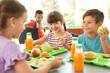 Leinwanddruck Bild - Children sitting at table and eating healthy food during break at school