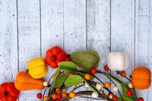Flat Lay Autumn Background With Felt Fuzzy Pumpkins In A Half Circle And Gourds Over A White Wooden Background. Fall Concept With Copy Space