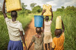 Leinwandbild Motiv Group of young African kids walking with buckets and jerrycans on their head as they prepare to bring clean water back to their village.