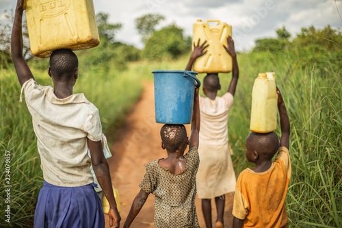 Acrylic Prints Africa Group of young African kids walking with buckets and jerrycans on their head as they prepare to bring clean water back to their village.