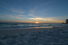 An Extravagant Sunset Over A Florida Beach In Panama City Turns The Sky Different Shades Of Yellow, Orange, Blue, Green, And Purple Surrounded By White But Soon Dark Clouds And Blue Ocean Waves Below.