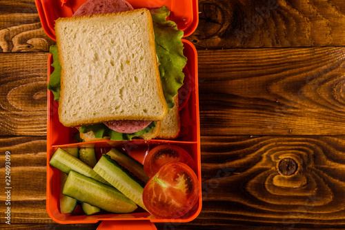 Lunch box with sandwich, cucumbers and tomatoes on wooden table. Top view