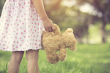 Rear View Of Little Girl Looking Her Future.Close Up Of Hands Of A Female Child Holding A Teddy Bear. Girl Standing Holding A Brown Furry Teddy Bear.Vintage Color