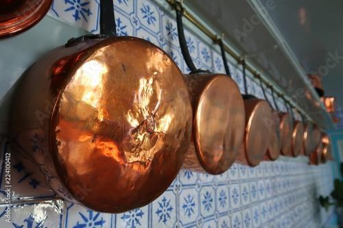 Set de vieilles casseroles en cuivre suspendues au mur d'une cuisine