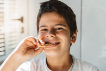 Smiling Kid With Braces Eating Biscuit For Breakfast