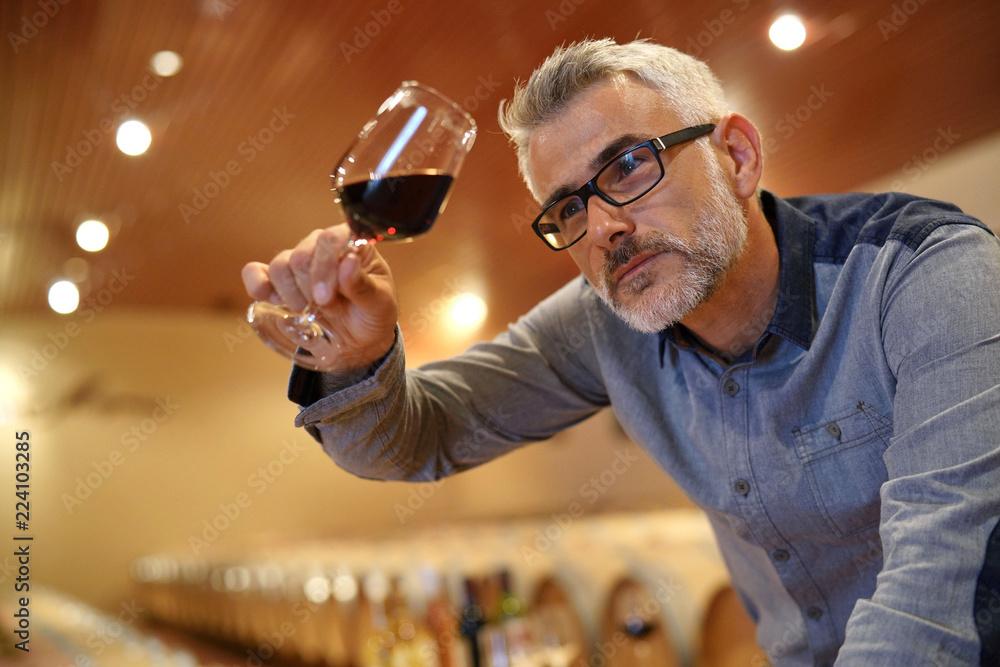 Fototapeta Winemaker tasting red wine in cellar