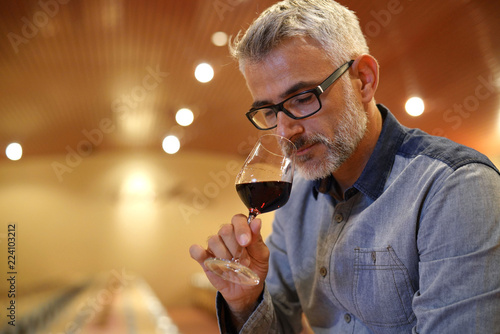 Fotografía Winemaker tasting red wine in cellar