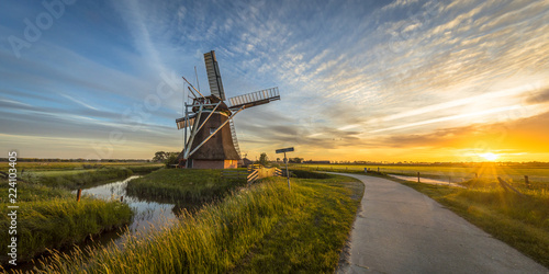 Wooden windmill with cycling track at sunset
